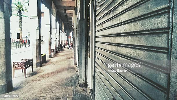 sidewalk by shops in city - 建具 シャッター ストックフォトと画像