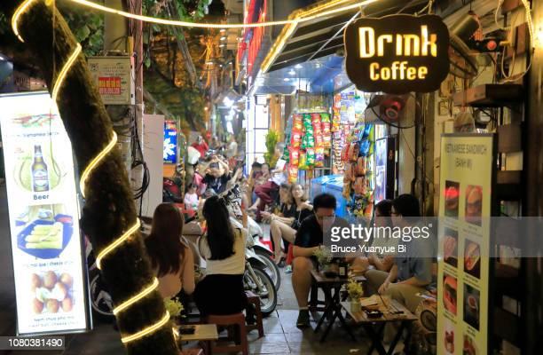 a sidewalk cafe at night - ハノイ ストックフォトと画像