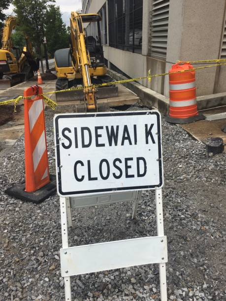 Sidewalk Closed Sign On Destroyed Sidewalk In Front Of Construction Equipment