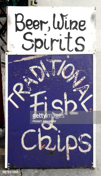 A sidewalk sign advertises a restaurant's fish and chips in London England