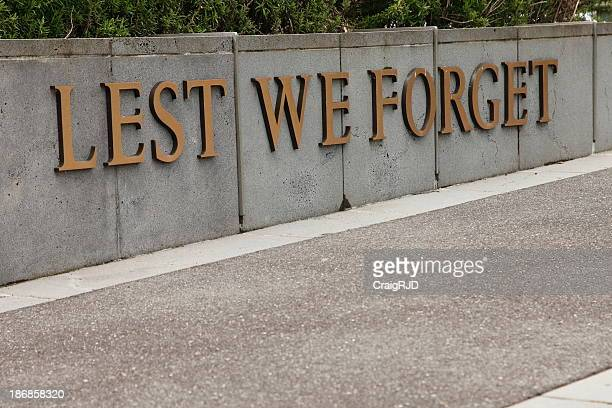 A sidewalk with a sign that says lest we forget