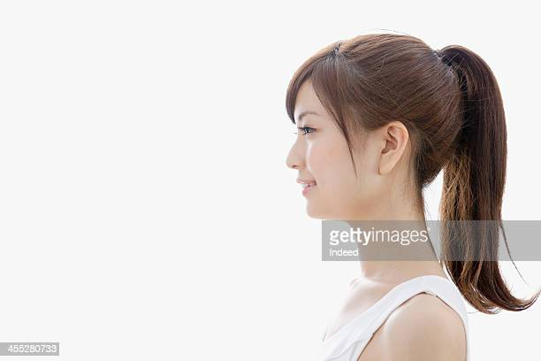 sideways-facing of woman dressed in tank top - 20代 ストックフォトと画像