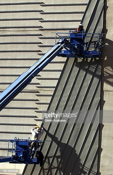 SIDEWorkers install siding on the parking lot being built at the corner of Broadway and 13th Ave as part of the Denver Art Museum's expansion project...