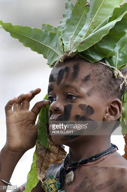 A Sidhi boy with painted face and wearing attached tree leaves clears his eye before he does a wild jungle dance in a getto in Junagadh city in the...