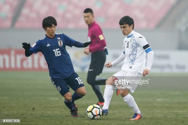 Sidikov Javokhir of Uzbekistan and Inoue Shion of Japan in action during AFC U23 Championship Quarterfinal between Japan and Uzbekistan at Jiangyin...