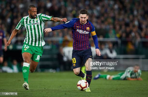 Sidnei Rechel of Real Betis competes for the ball with Lionel Messi of FC Barcelona during the La Liga match between Real Betis Balompie and FC...