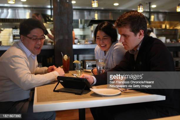 Sidney Chen , Cindy Matsuyama , and Ivan Tsurikov look over a new tablet that restaurants can put at every table for do-it-yourself ordering, paying...