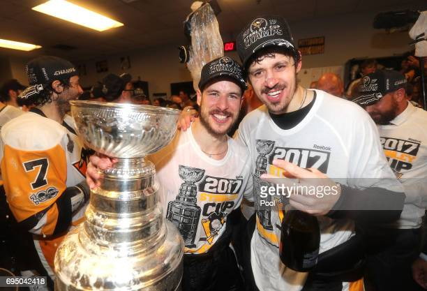 Sidney Crosby and Evgeni Malkin of the Pittsburgh Penguins celebrate with the Stanley Cup in the locker room after Game Six of the 2017 NHL Stanley...