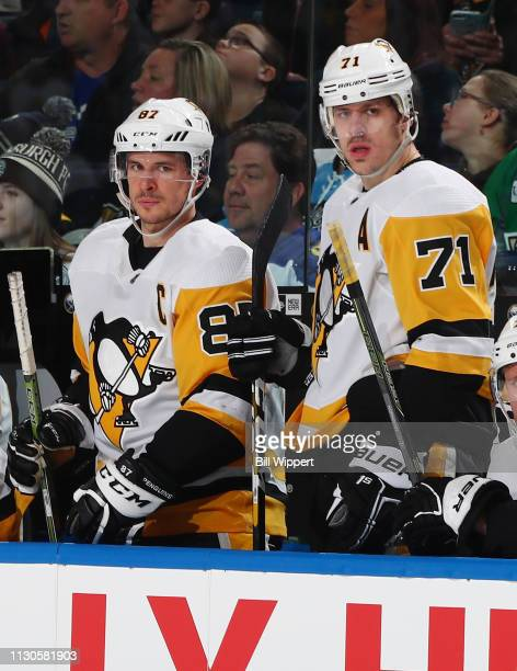 Sidney Crosby and Evgeni Malkin of the Pittsburgh Penguins follow the play from the bench during an NHL game against the Buffalo Sabres on March 14...