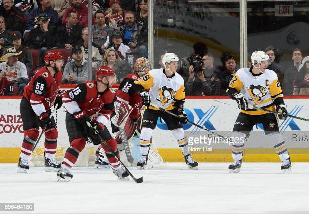 Sidney Crosby and Jake Guentzel of the Pittsburgh Penguins battle for position with Jason Demers and Brad Richardson of the Arizona Coyotes in front...