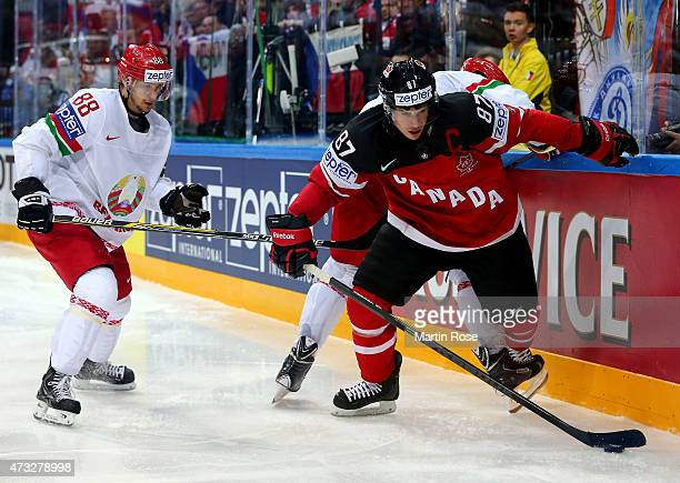Sidney Crosby of Canada and Yevgeni Kovyrshin of Belarus battle for the puck during the IIHF World Championship quarter final match between Canada...