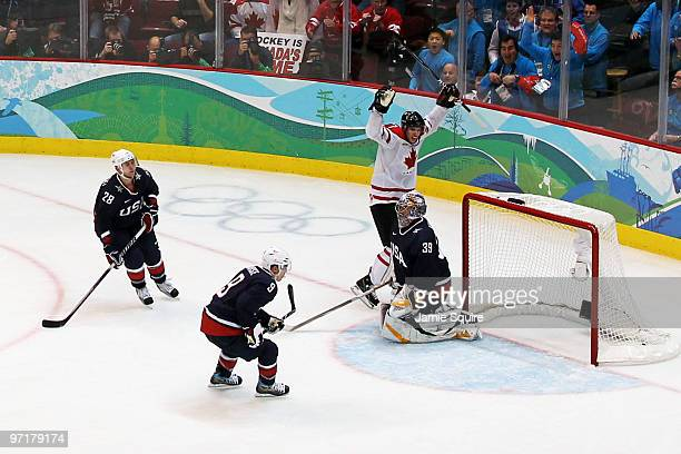 Sidney Crosby of Canada celebrates after scoring the matchwinning goal in overtime whilst dejected Team USA players look on during the ice hockey...