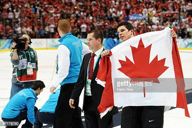 Sidney Crosby of Canada celebrates with his national flag after scoring the matchwinning goal in overtime during the ice hockey men's gold medal game...