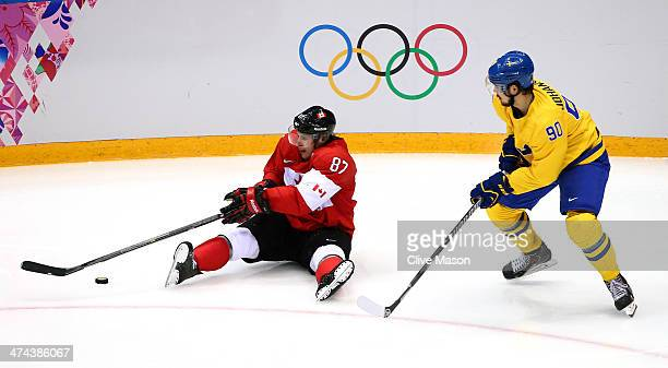 Sidney Crosby of Canada controls the puck as Marcus Johansson of Sweden closes in during the Men's Ice Hockey Gold Medal match on Day 16 of the 2014...