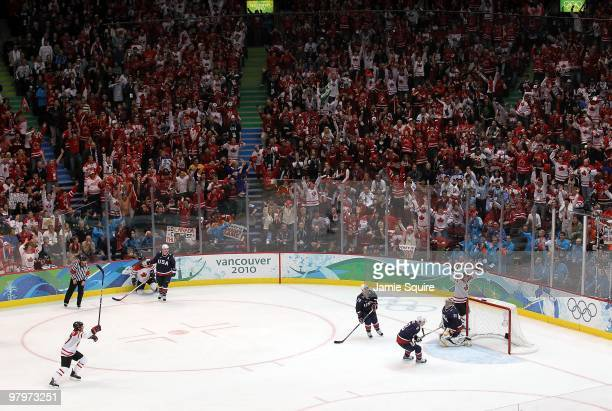 Sidney Crosby of Canada raises his arms to celebrate after scoring the gamewinning goal in overtime against Ryan Miller of USA in the ice hockey...
