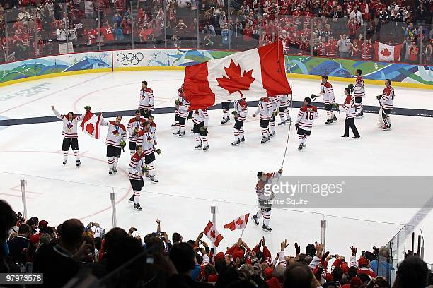 Sidney Crosby of Canada skates with the Canadian national flag following Canada's 32 overtime victory during the ice hockey men's gold medal game...