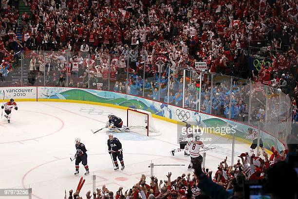 Sidney Crosby of Canada waits to celebrate in the corner with teammates after scoring the game-winning goal in overtime against Ryan Miller of USA in...