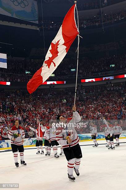 Sidney Crosby of Canada waves a national flag following his team's 31 overtime victory during the ice hockey men's gold medal game between USA and...