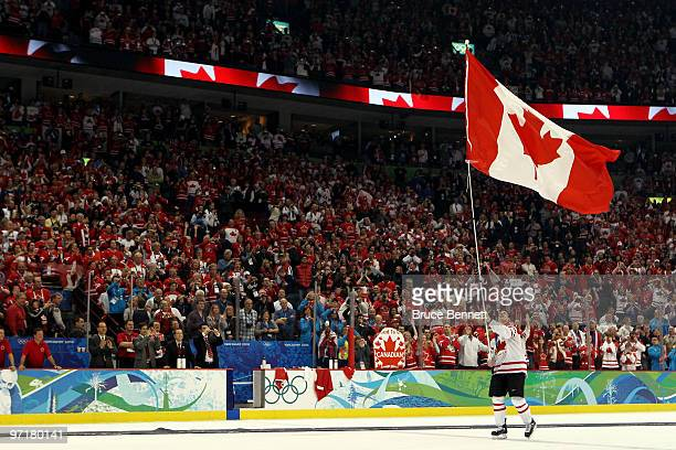 Sidney Crosby of Canada waves a national flag following his team's 32 overtime victory during the ice hockey men's gold medal game between USA and...