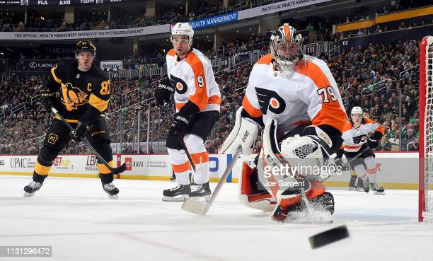 Sidney Crosby of the Pittsburgh Penguins and Ivan Provorov of the Philadelphia Flyers and Carter Hart of the Philadelphia Flyers eye the puck at PPG...