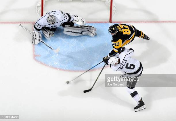Sidney Crosby of the Pittsburgh Penguins and Jake Muzzin of the Los Angeles Kings battle or the puck in front of Jonathan Quick of the Los Angeles...