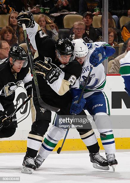 Sidney Crosby of the Pittsburgh Penguins and Linden Vey of the Vancouver Canucks battle for the loose puck during the third period at Consol Energy...