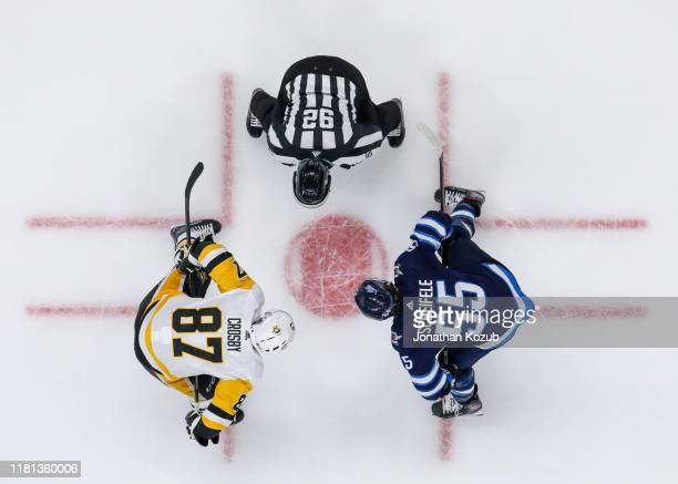 Sidney Crosby of the Pittsburgh Penguins and Mark Scheifele of the Winnipeg Jets get set for a second period face-off at the Bell MTS Place on...