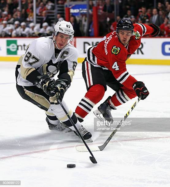 Sidney Crosby of the Pittsburgh Penguins and Niklas Hjalmarsson of the Chicago Blackhawks battle for the puck at the United Center on January 6 2016...