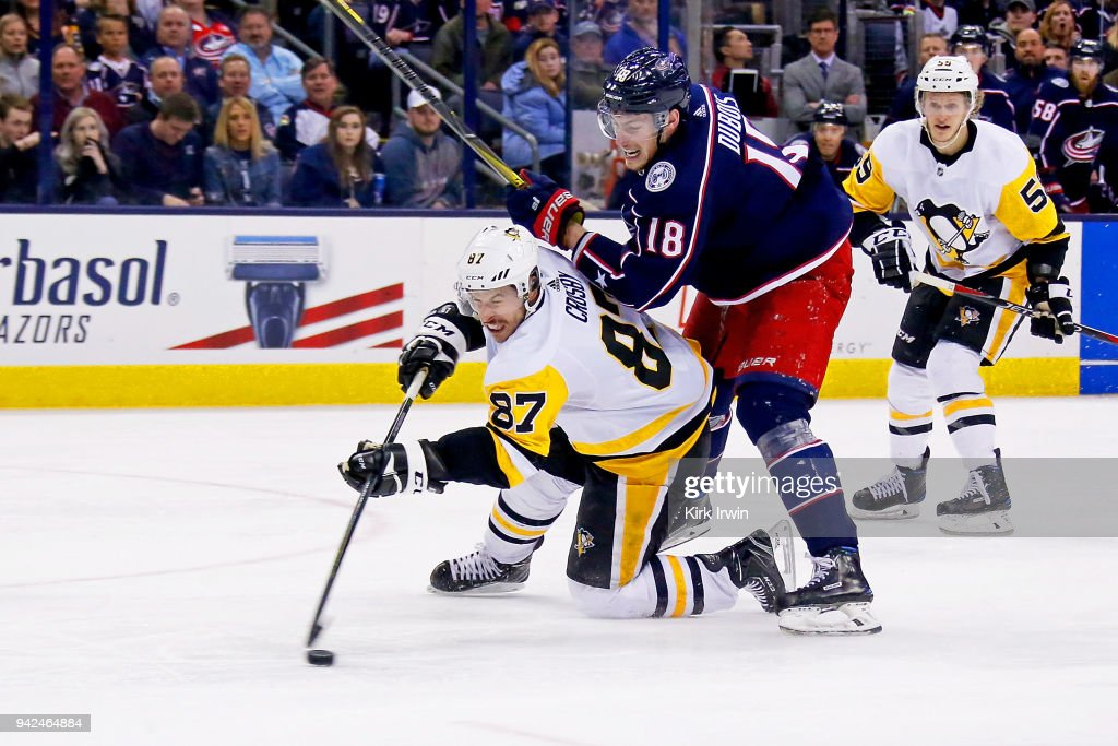 Sidney Crosby #87 of the Pittsburgh Penguins and Pierre-Luc Dubois #18 of the Columbus Blue Jackets battle for control of the puck during the third period on April 5, 2018 at Nationwide Arena in Columbus, Ohio. Pittsburgh defeated Columbus 5-4 in overtime.