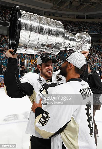 Sidney Crosby of the Pittsburgh Penguins ands off the Stanley Cup to teammate Trevor Daley after the Penguins won Game 6 of the 2016 NHL Stanley Cup...