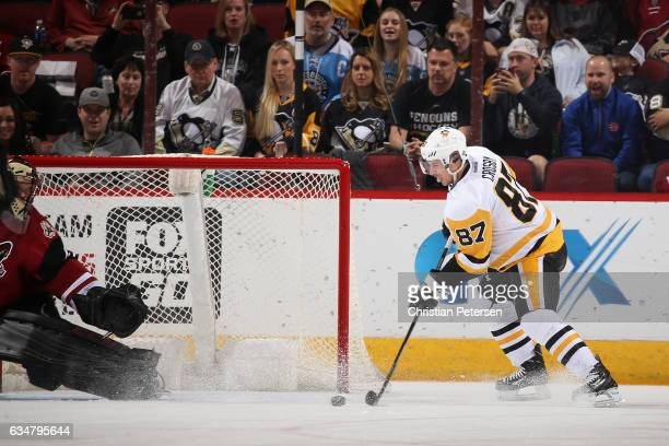 Sidney Crosby of the Pittsburgh Penguins attempts to control the puck for a shot against the Arizona Coyotes during the first period of the NHL game...