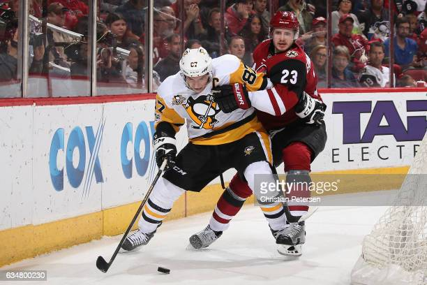 Sidney Crosby of the Pittsburgh Penguins attempts to control the puck under pressure from Oliver EkmanLarsson of the Arizona Coyotes during the...