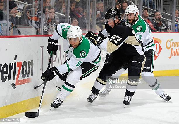 Sidney Crosby of the Pittsburgh Penguins battles for the loose puck between the defense of Trevor Daley and Alex Goligoski of the Dallas Stars on...