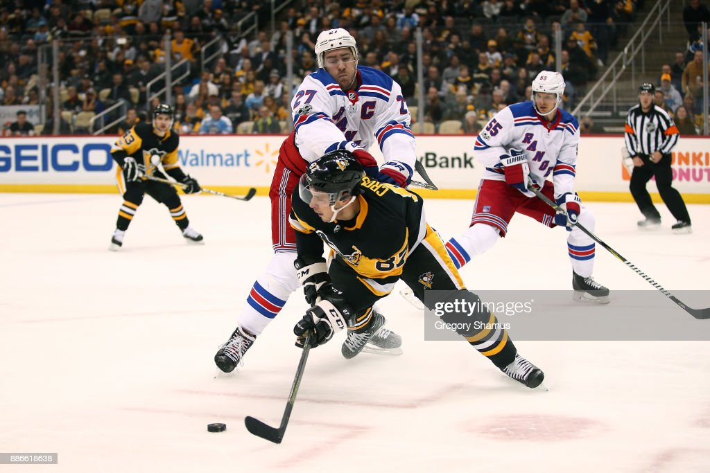 Sidney Crosby #87 of the Pittsburgh Penguins battles for the puck with Ryan McDonagh #27 of the New York Rangers during the second period at PPG PAINTS Arena on December 5, 2017 in Pittsburgh, Pennsylvania.