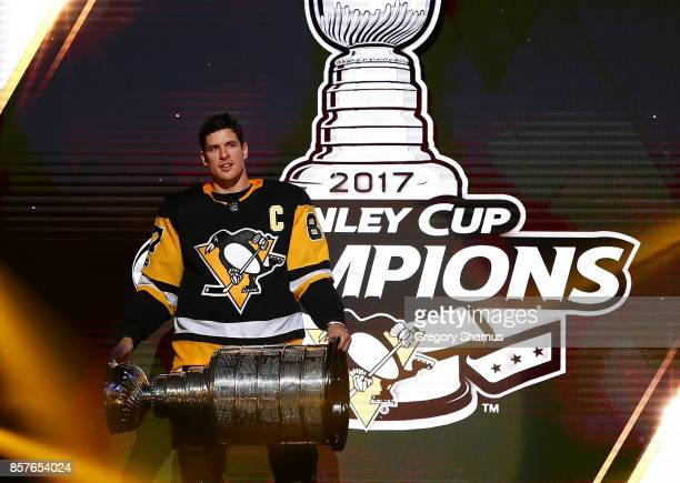 Sidney Crosby of the Pittsburgh Penguins brings the Stanley Cup to the ice before to raising their 2017 championship banner prior to playing the St...