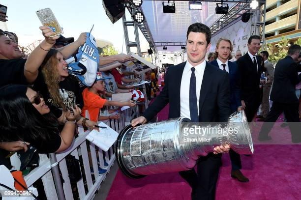 Sidney Crosby of the Pittsburgh Penguins carries the Stanley Cup as he arrives at the 2017 NHL Awards at T-Mobile Arena on June 21, 2017 in Las...