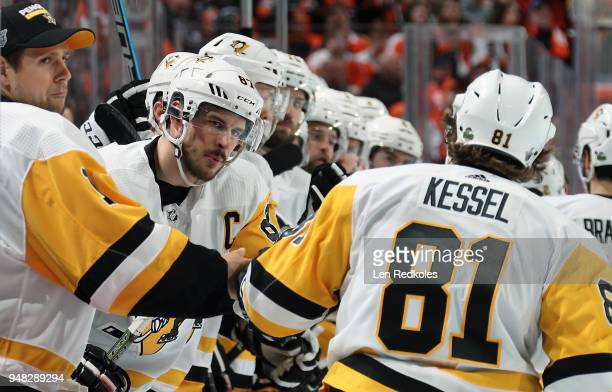 Sidney Crosby of the Pittsburgh Penguins celebrates a second period goal from the bench with teammate Phil Kessel against the Philadelphia Flyers in...