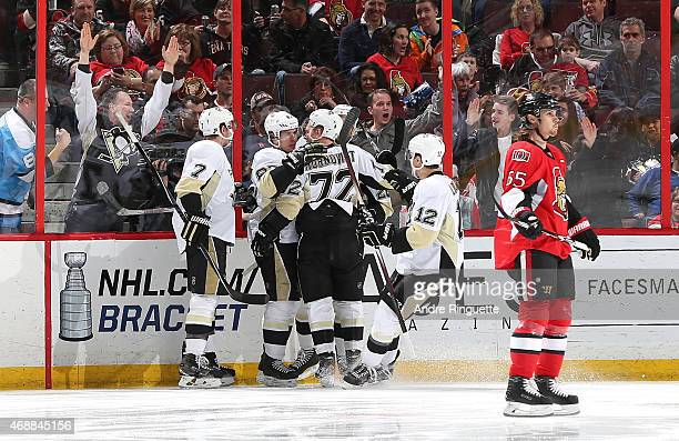 Sidney Crosby of the Pittsburgh Penguins celebrates his first period goal with teammates Paul Martin Patric Hornqvist and Ben Lovejoy as Erik...
