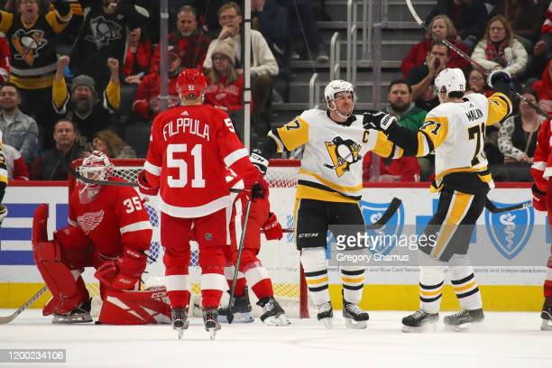 Sidney Crosby of the Pittsburgh Penguins celebrates his game winning overtime goal with Evgeni Malkin next to Jimmy Howard of the Detroit Red Wings...