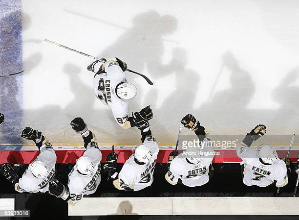 Sidney Crosby of the Pittsburgh Penguins celebrates his second period assist against the Ottawa Senators at the players' bench at Scotiabank Place on...
