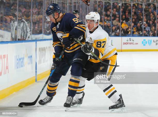 Sidney Crosby of the Pittsburgh Penguins checks Rasmus Ristolainen of the Buffalo Sabres during an NHL game on December 1 2017 at KeyBank Center in...
