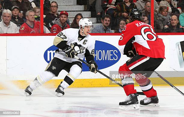 Sidney Crosby of the Pittsburgh Penguins controls the puck looking to make a pass against Erik Karlsson of the Ottawa Senators at Canadian Tire...