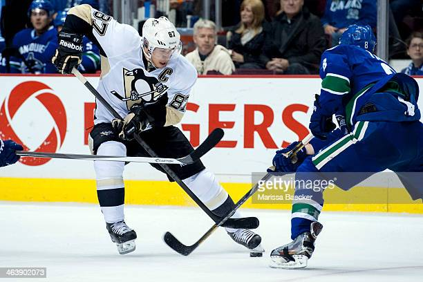 Sidney Crosby of the Pittsburgh Penguins dangles the puck around Yannick Weber of the Vancouver Canucks on January 7, 2014 at Rogers Arena in...
