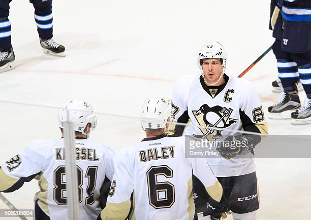 Sidney Crosby of the Pittsburgh Penguins discusses strategy with teammates Phil Kessel and Trevor Daley during a second period stoppage in play...