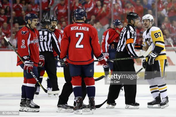 Sidney Crosby of the Pittsburgh Penguins exchanges words with Matt Niskanen and Dmitry Orlov of the Washington Capitals in the first period of Game...