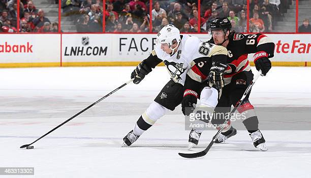 Sidney Crosby of the Pittsburgh Penguins fends off Erik Karlsson of the Ottawa Senators as he controls the puck at Canadian Tire Centre on February...