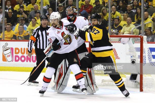 Sidney Crosby of the Pittsburgh Penguins fights for position against Erik Karlsson of the Ottawa Senators during the third period in Game One of the...