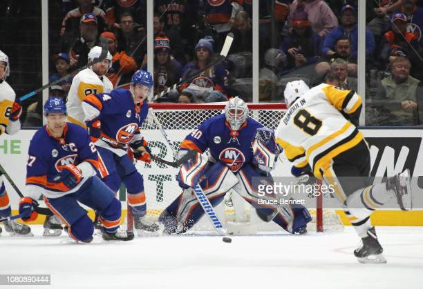 Sidney Crosby of the Pittsburgh Penguins flies past Robin Lehner of the New York Islanders as the save is made at NYCB Live at the Nassau Coliseum on...