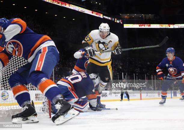 Sidney Crosby of the Pittsburgh Penguins flies past Robin Lehner of the New York Islanders at NYCB Live at the Nassau Coliseum on December 10 2018 in...