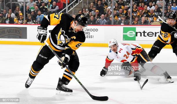 Sidney Crosby of the Pittsburgh Penguins handles the puck against Travis Hamonic of the Calgary Flames at PPG Paints Arena on March 5 2018 in...